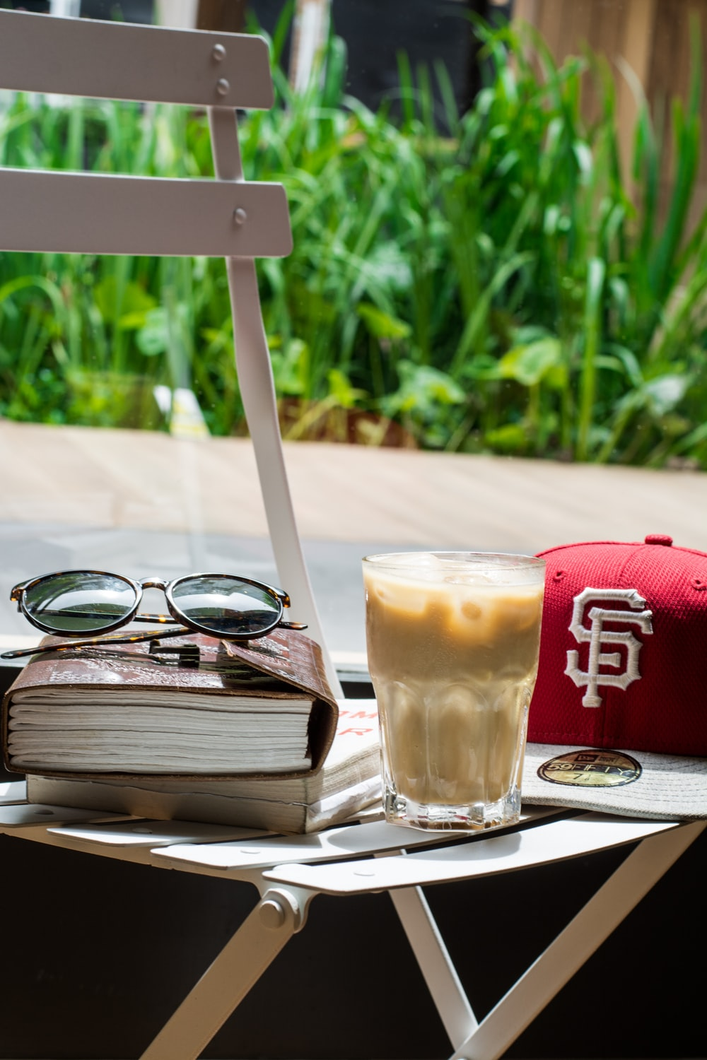red cap, drinking glass, brown, book, and black sunglasses on top of white table