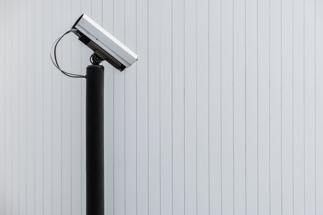 A surveillance camera in front of a minimalistic background