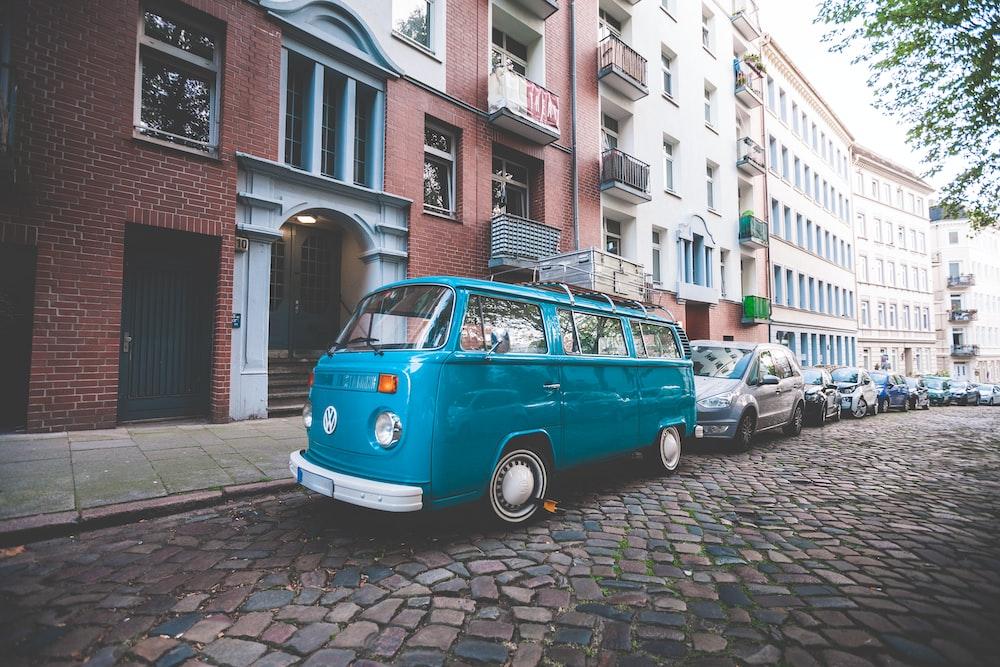blue van beside paved road