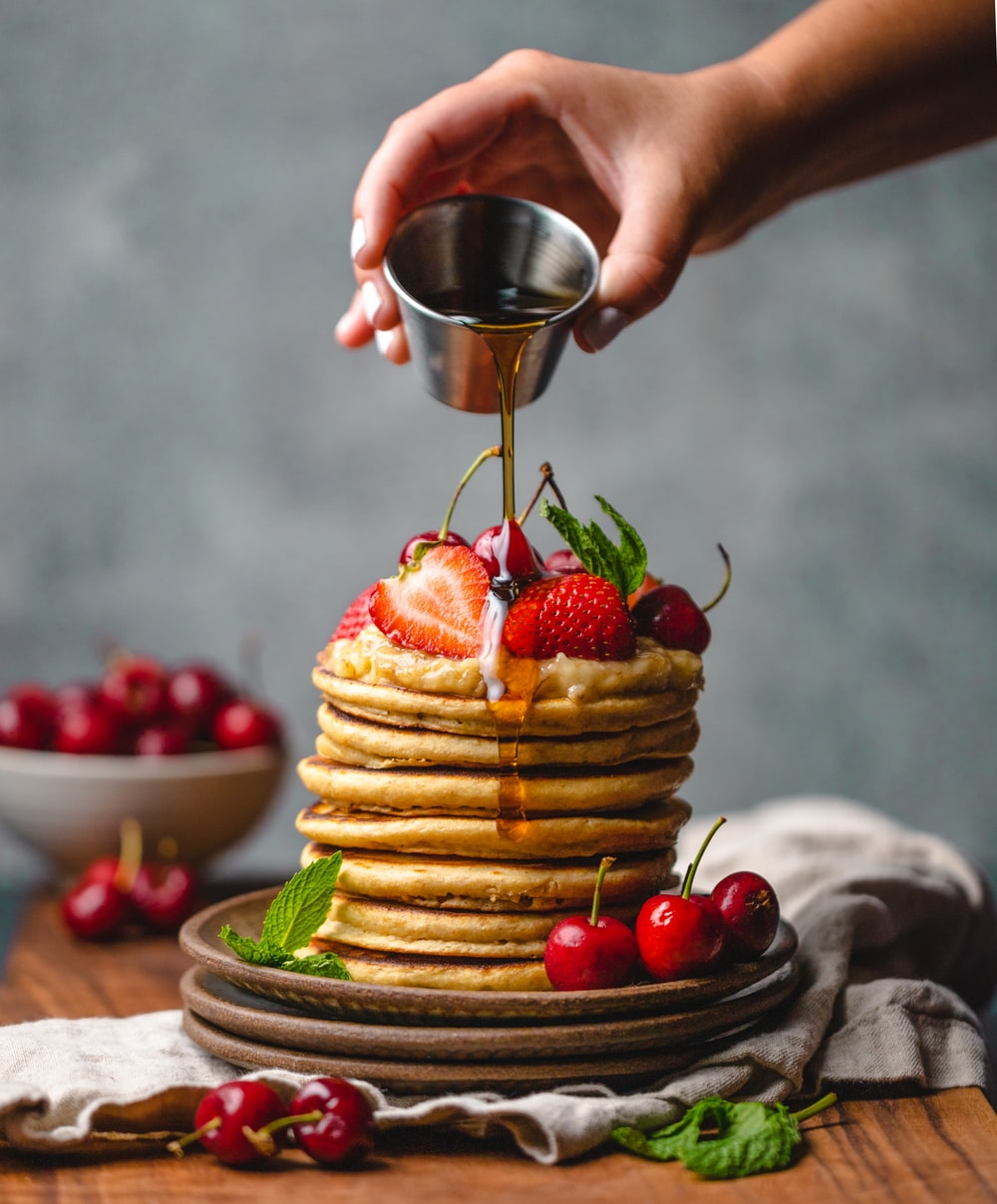 person pouring syrup on pancake