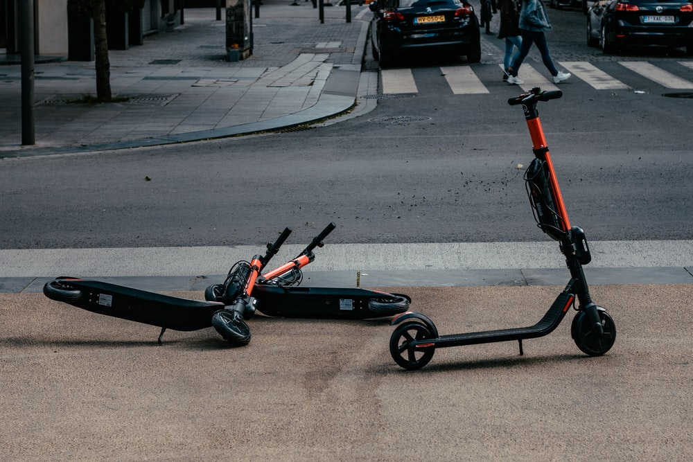 motorized scooters parked near road during daytime