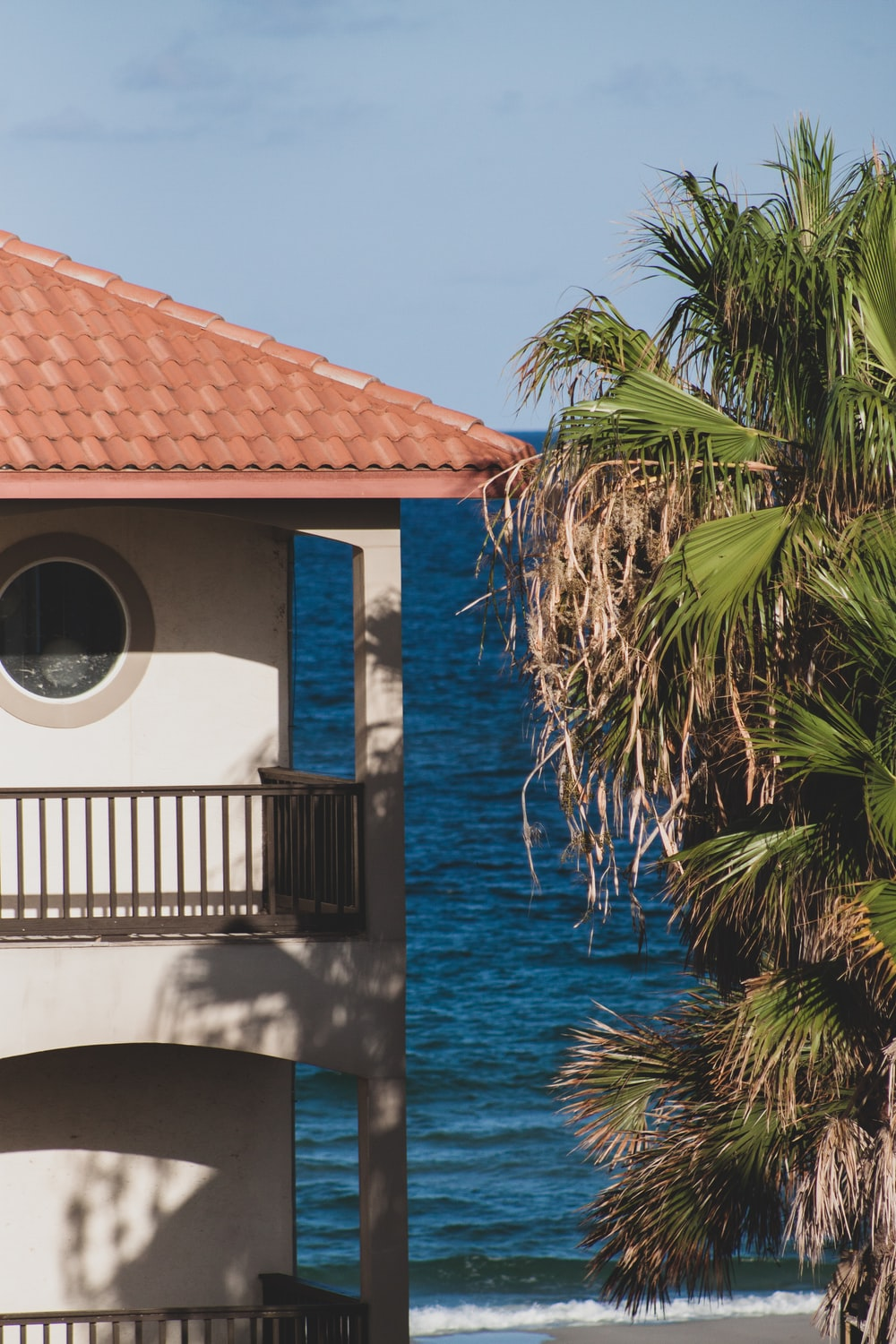 building with balcony and porch beside tree in front of the sea during day
