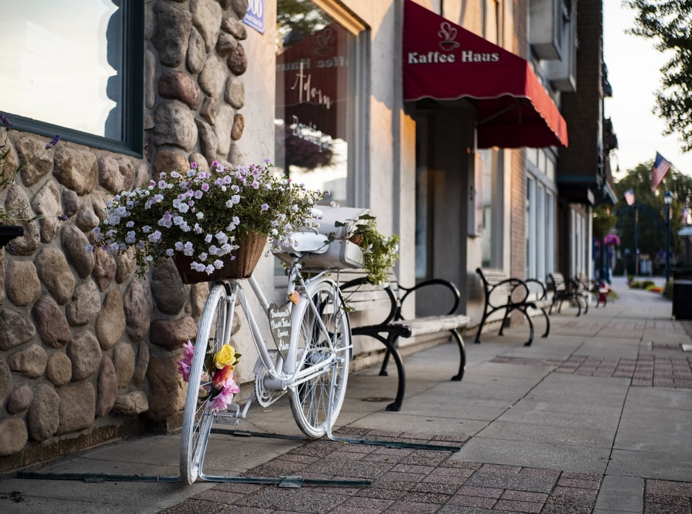 white bicycle parked standing near store