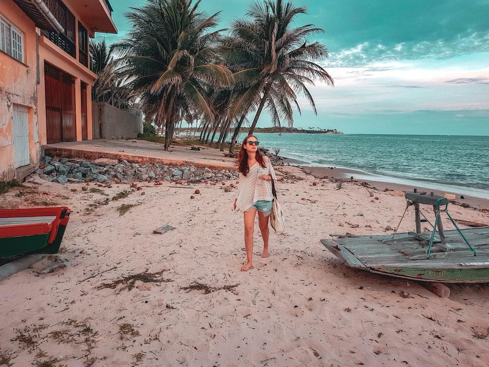 woman walking on seashore walking near boat