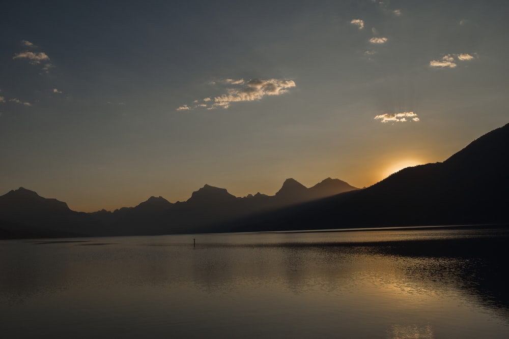 silhouette of mountain and calm water