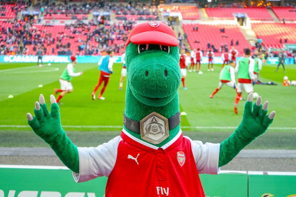 green animal mascot standing near field