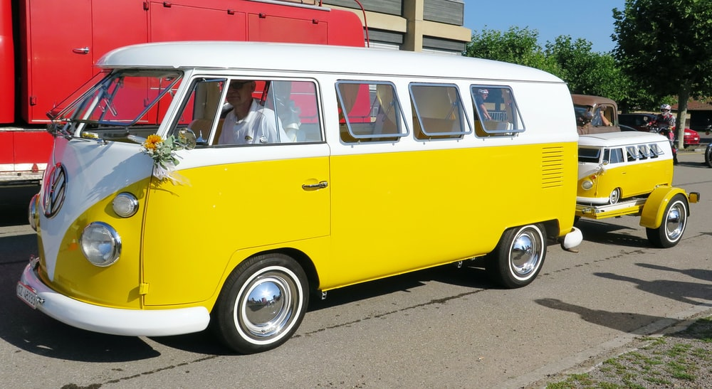 yellow and white Volkswagen bus on road