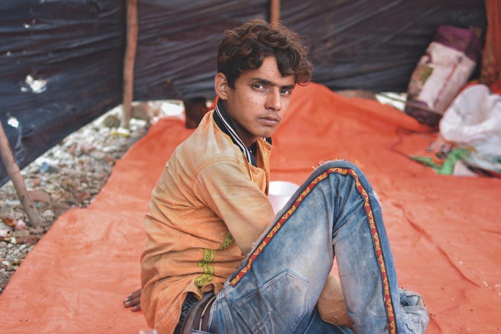man wearing blue jeans sitting on orange textile