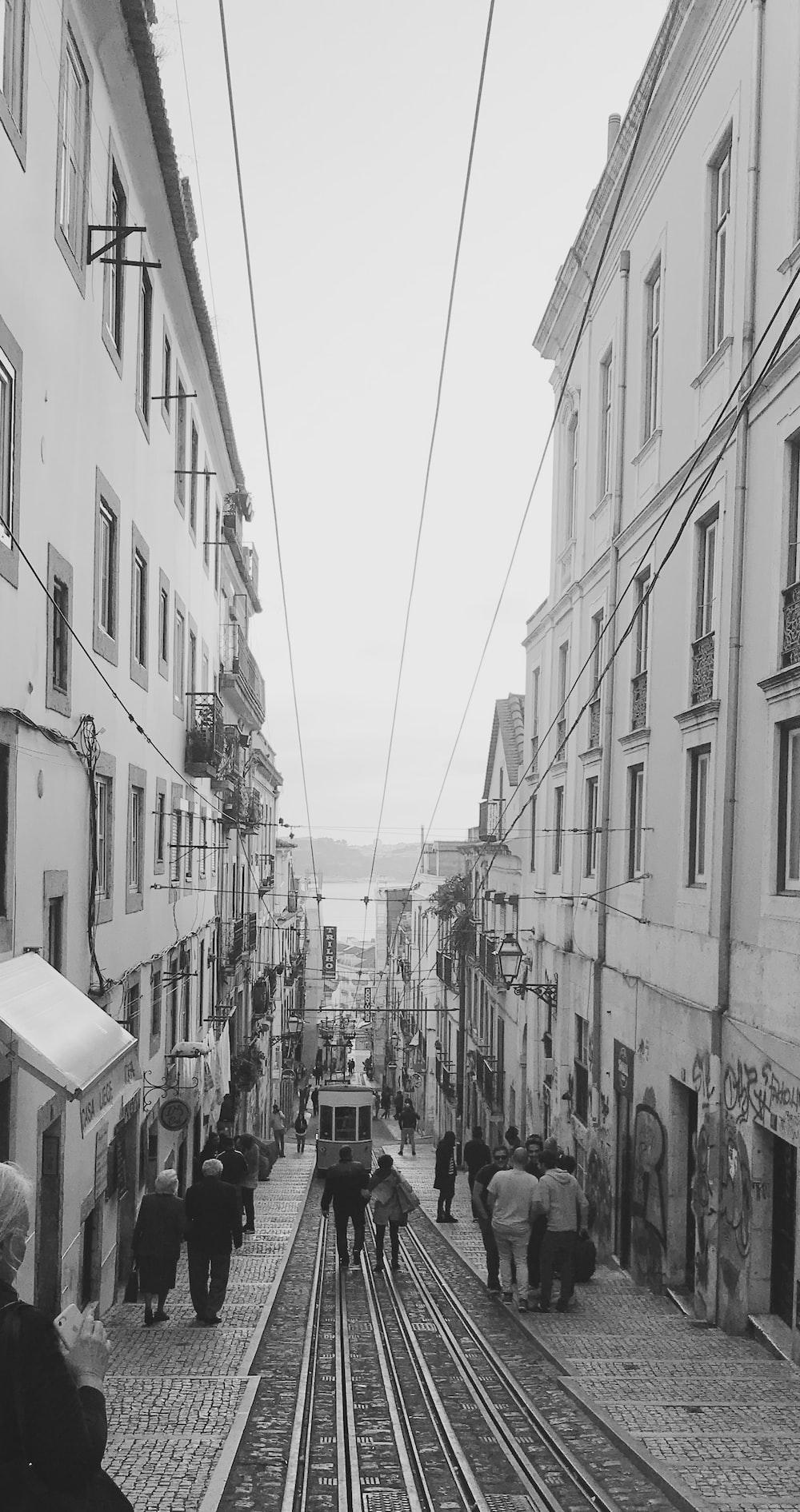 grayscale photo of people walking between buildings