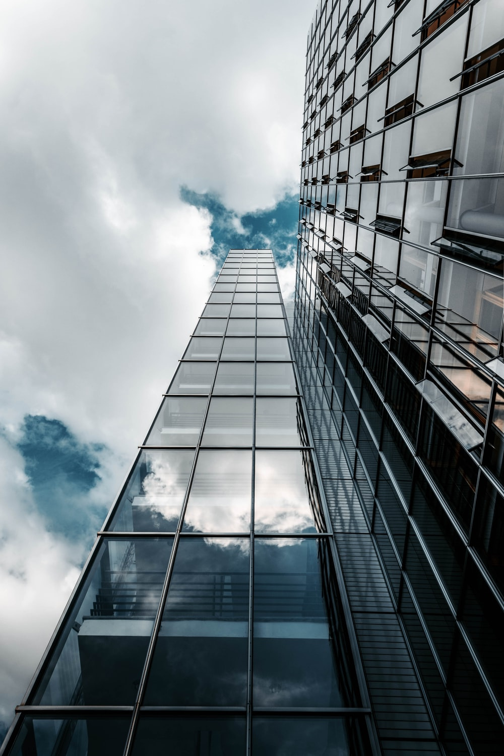 low angle photography of high rise building under cloudy sky
