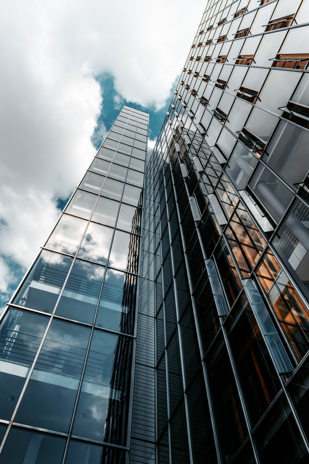 low angle photography of glass building under cloudy sky