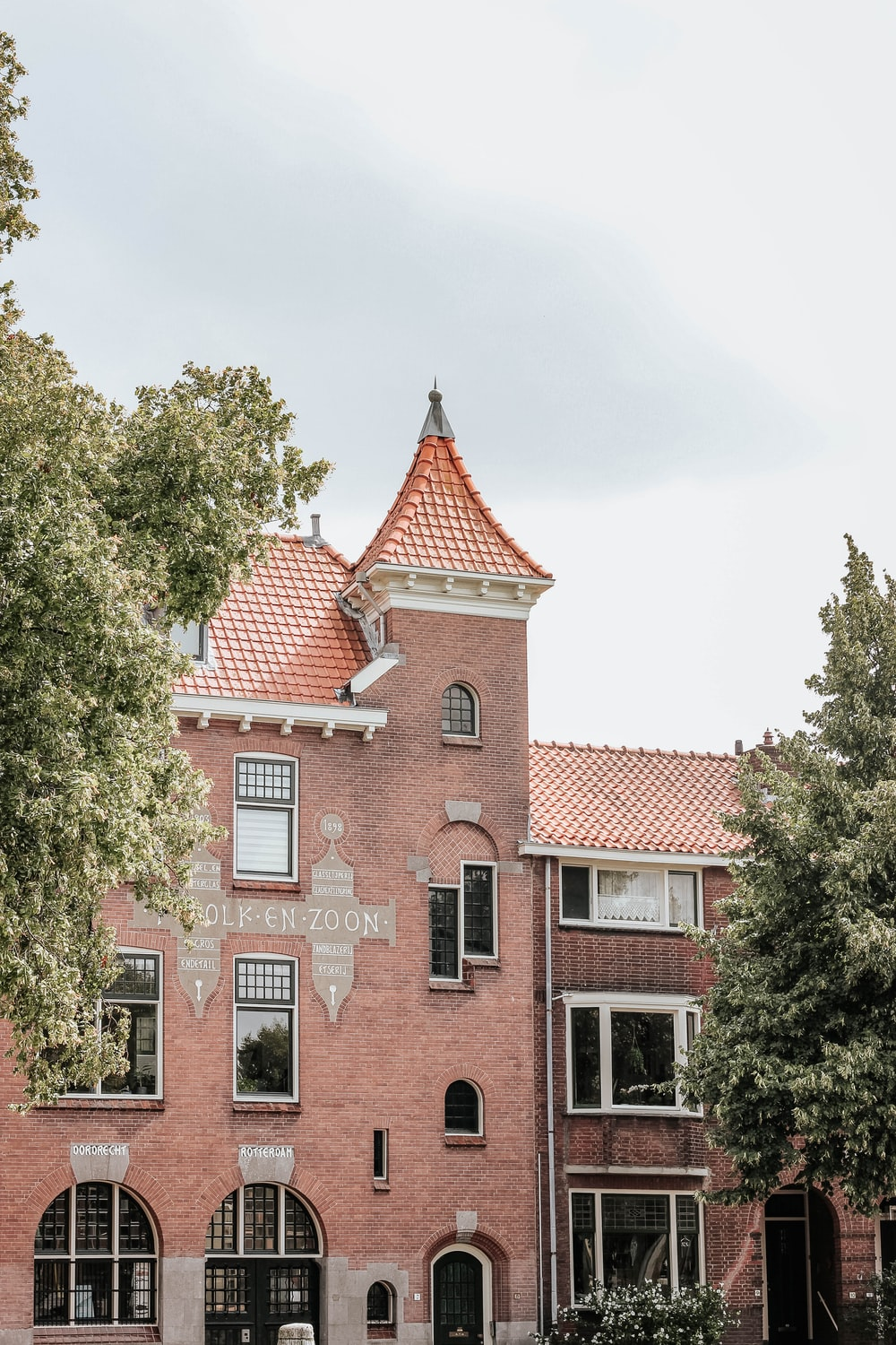 red brick building standing near trees under cloudy sky