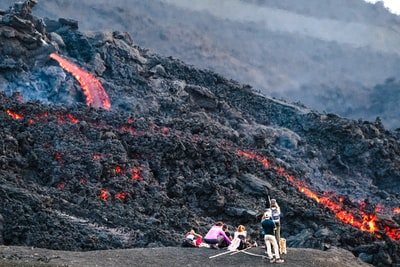 photography of people standing beside lava during daytime
