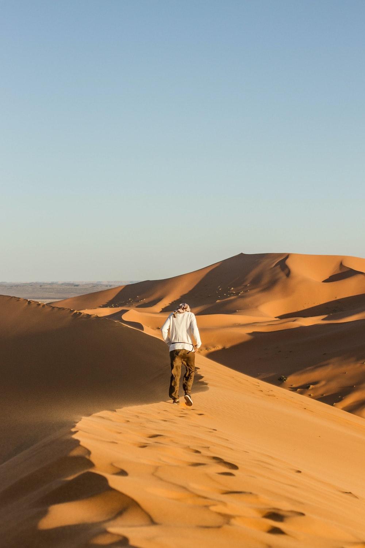 man walking on desert during daytime