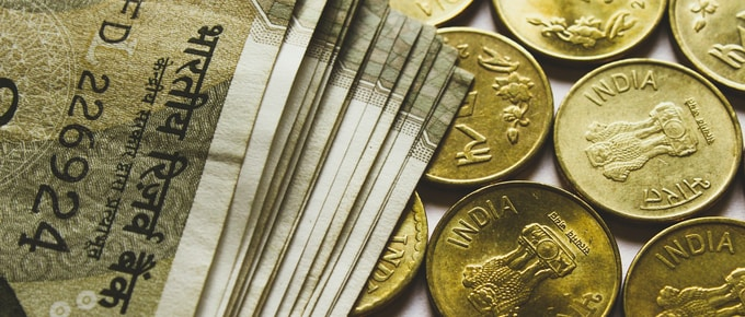 round gold-colored rupee coins and banknotes