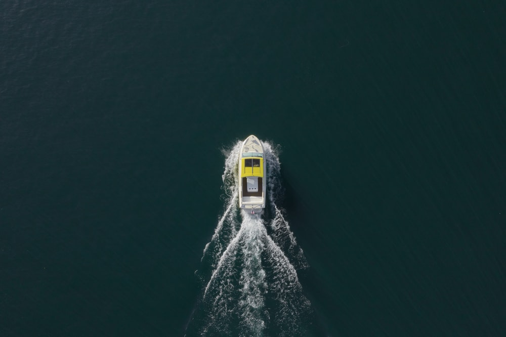 aerial photo of white and yellow motorboat