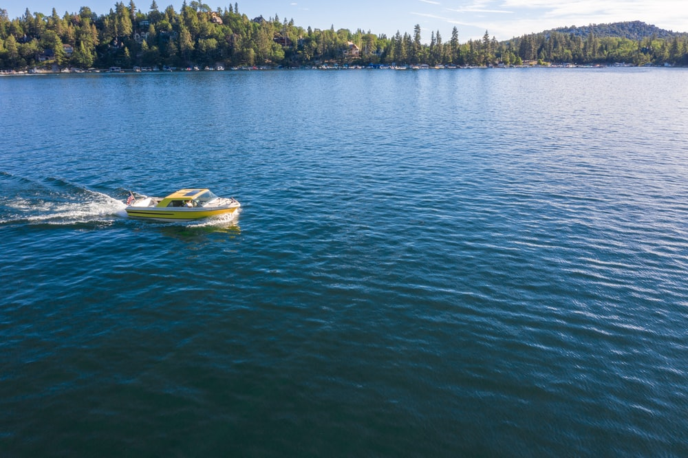 yellow and white boat on body of water at daytime