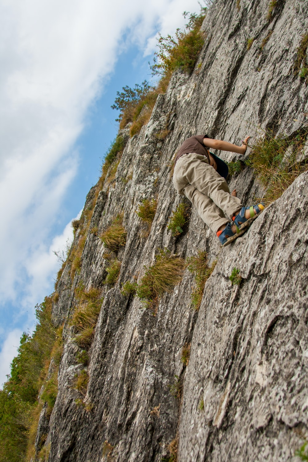 person climbing on cliff during day time