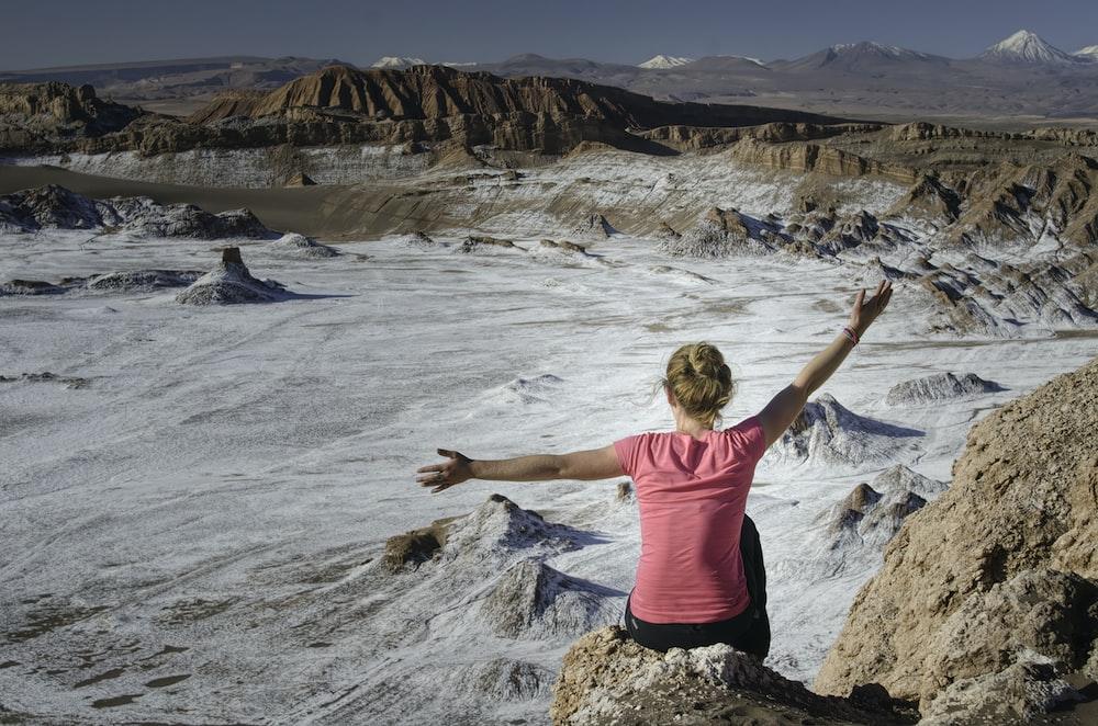 woman wearing pink shirt sitting on rock