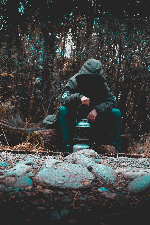 man sitting on rock holding lantern