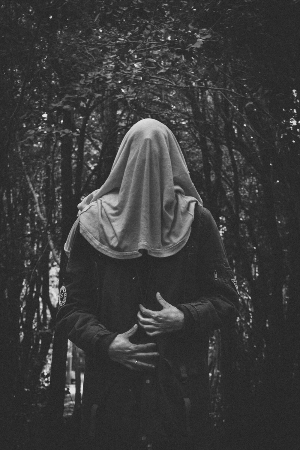 grayscale photo of man covering his face under tree