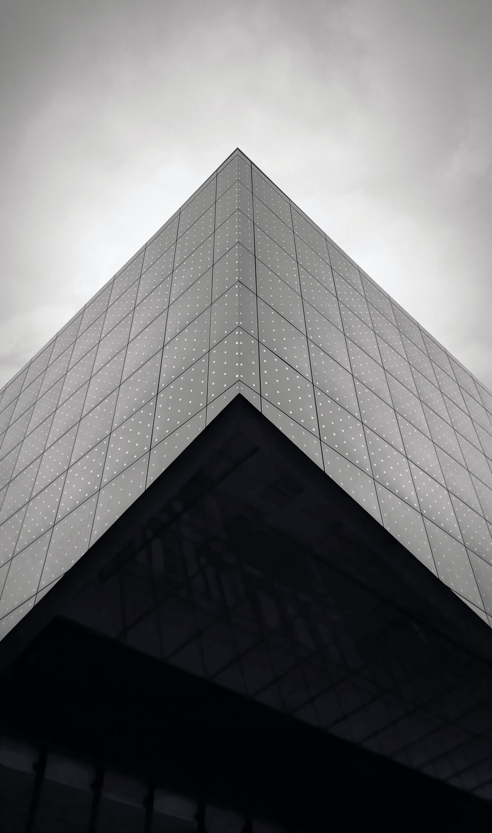 low angle grayscale photography of glass building