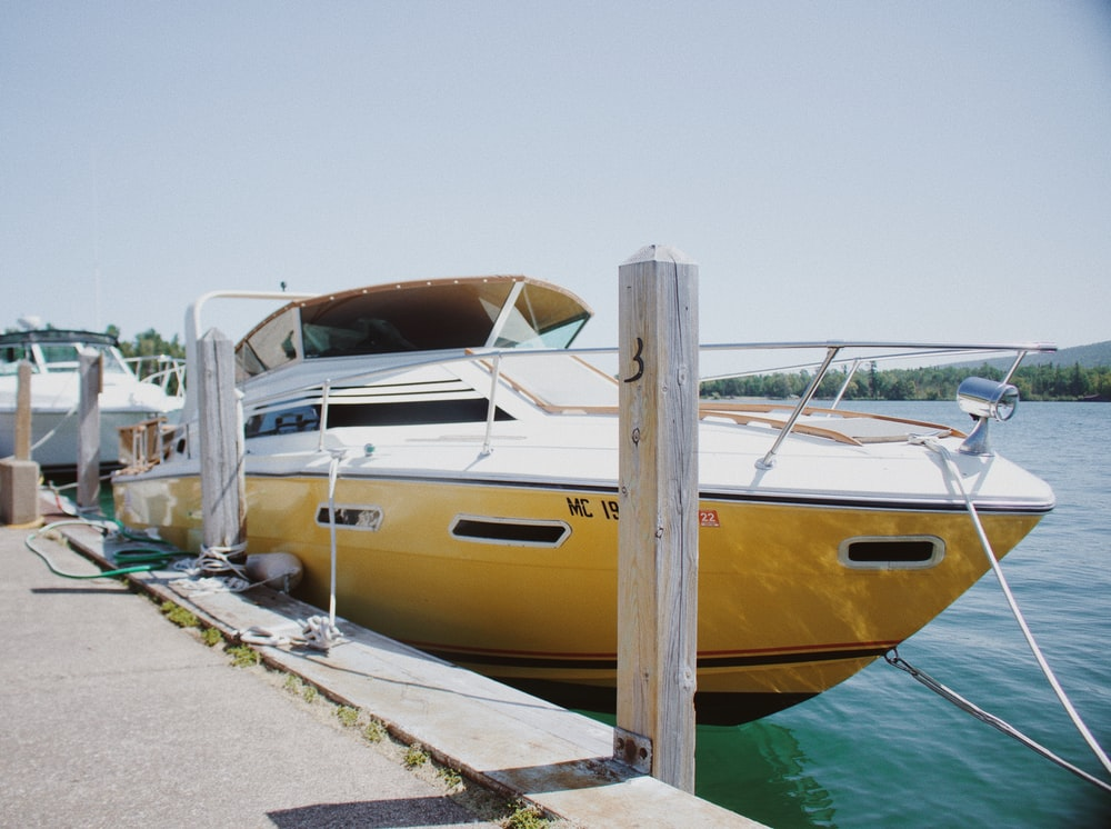 yellow and white yacht on body of water