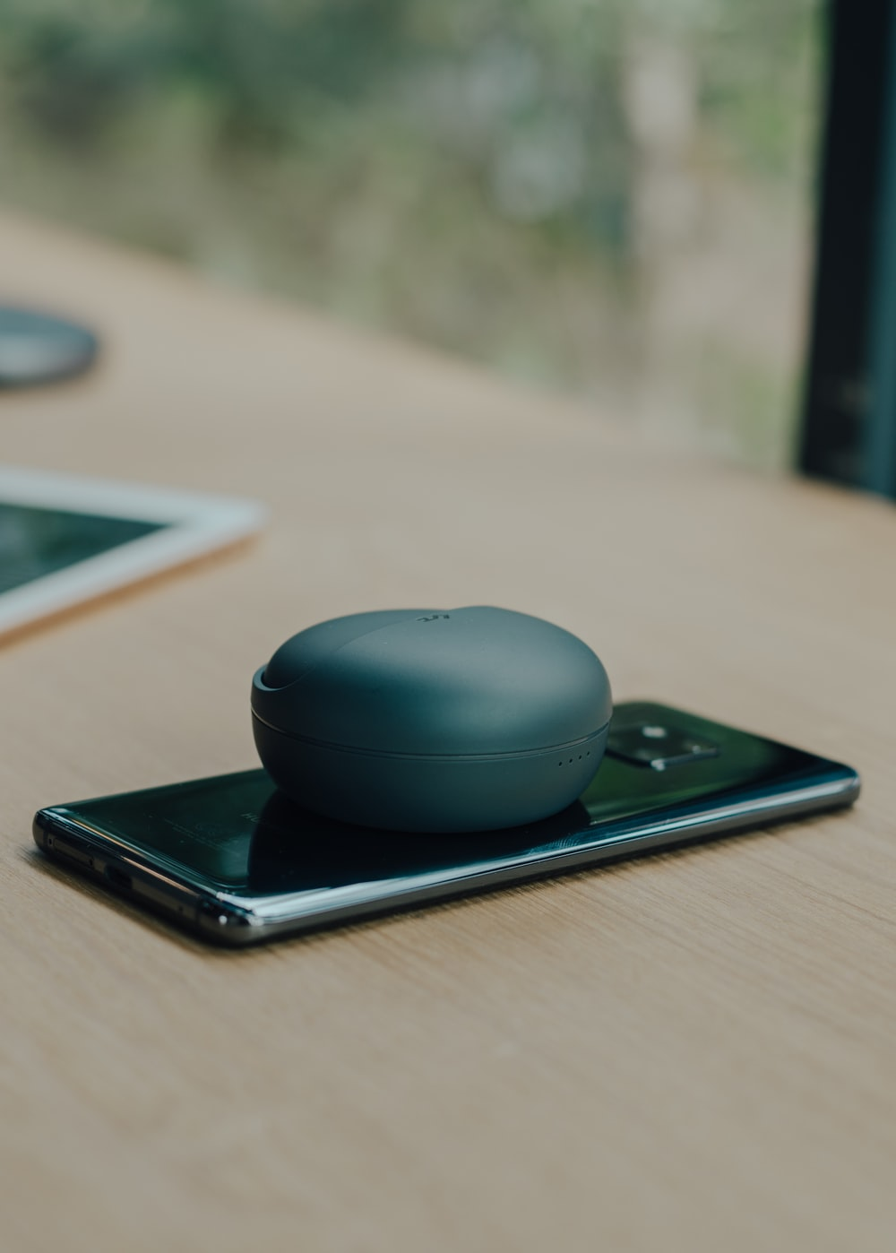 round black wireless portable speaker on Android smartphone