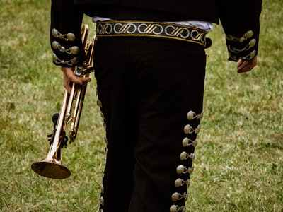 close-up photography of person holding trombone mariachi teams background