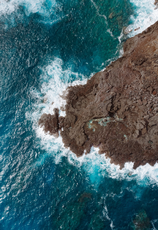 bird's-eye view of brown rocks on body of water
