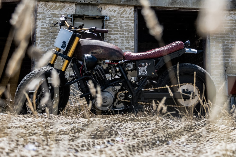 black and brown motorcycle parked besides white and brown concrete house