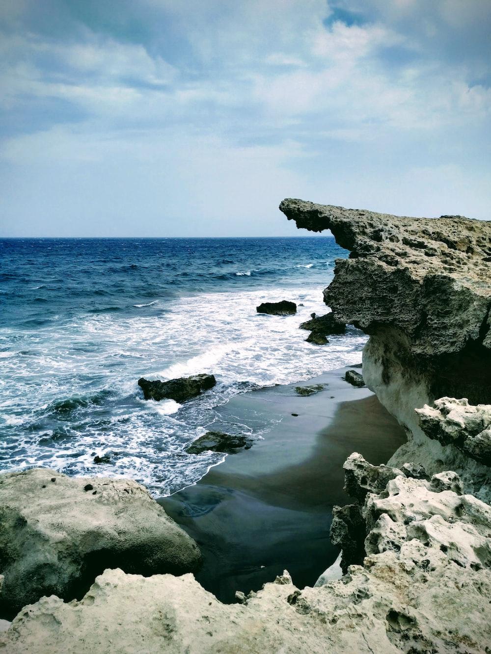 gray large stone on seashore