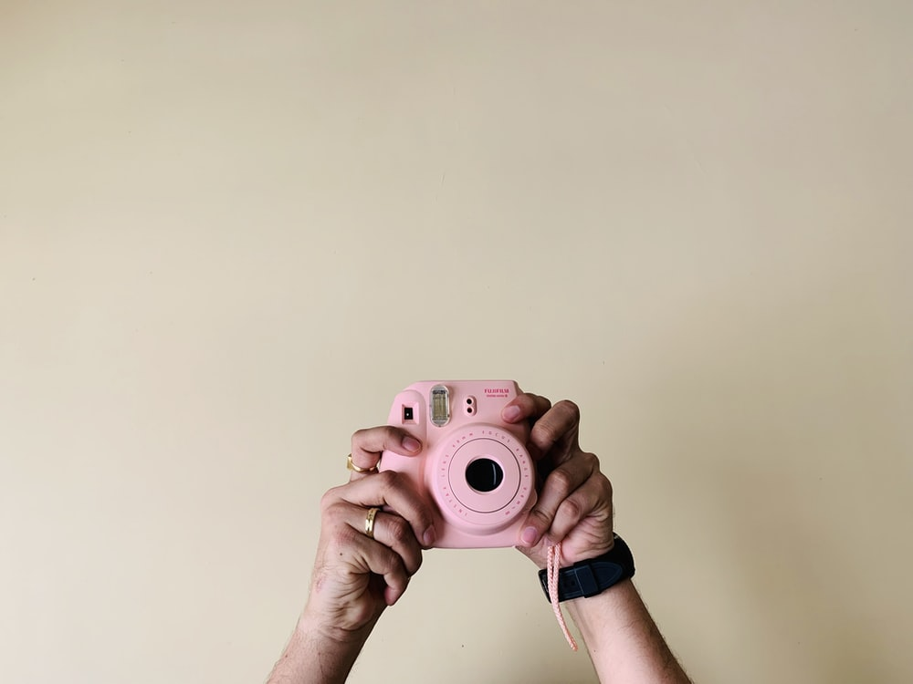 person holding pin camera