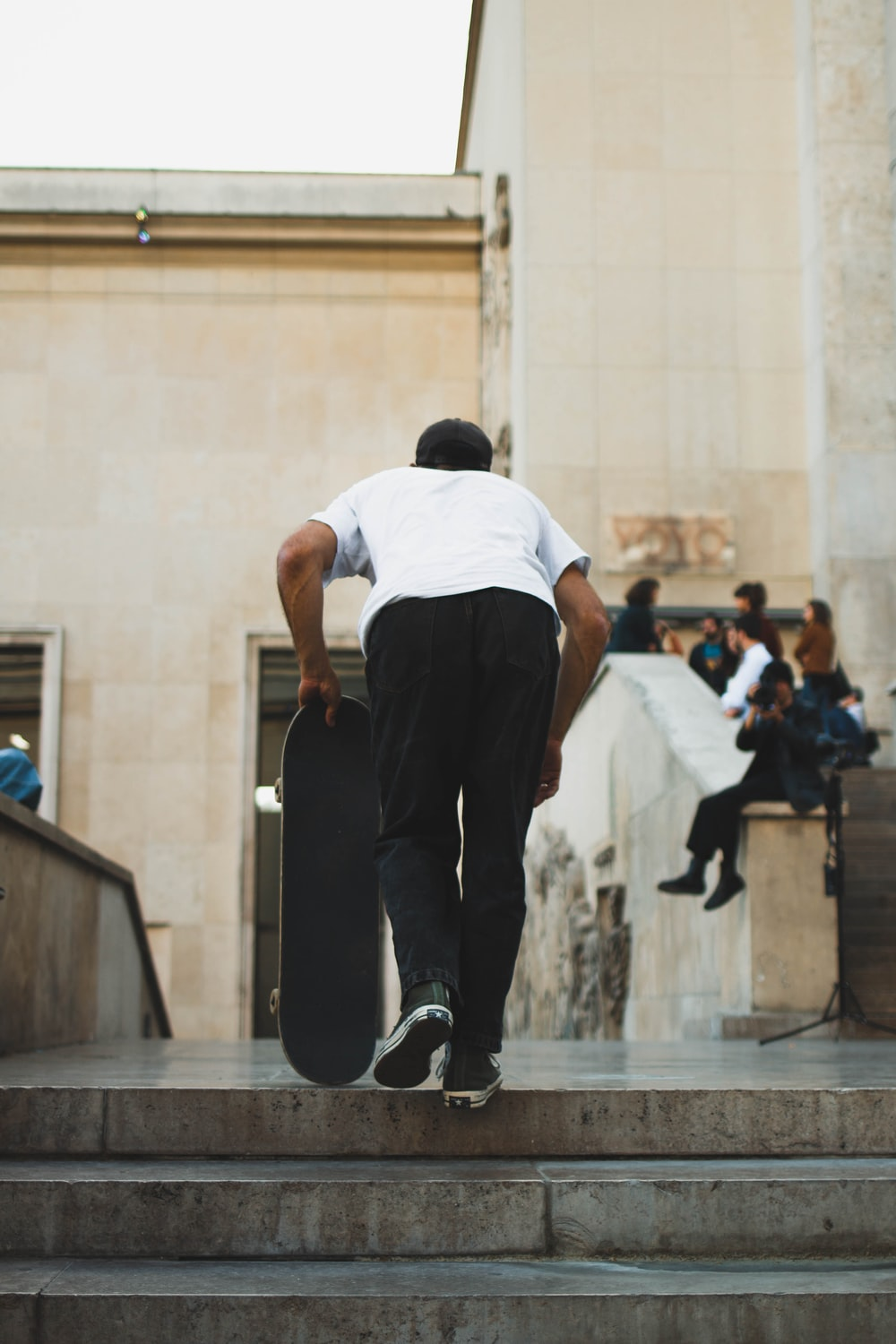 man in white t-shirt and black pants holding skateboard
