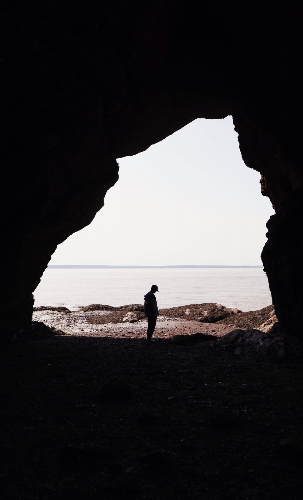 silhouette of person standing on cave entrance across horizon