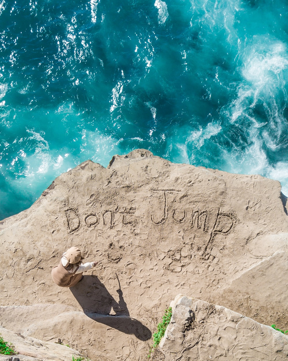 person standing on cliff writing don't jump on ground