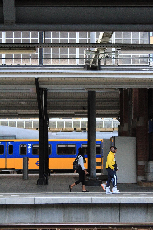 two persons walking beside train rail