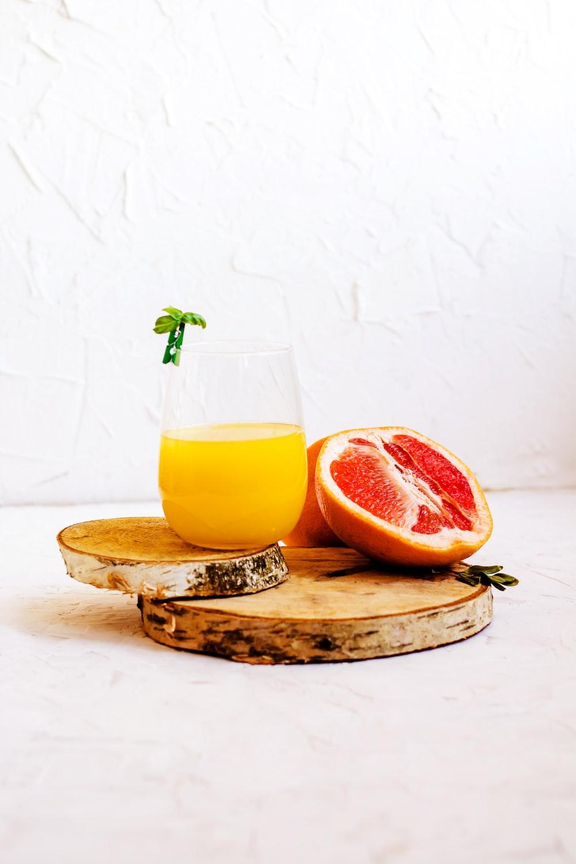 glass of orange drink and sliced grapefruit