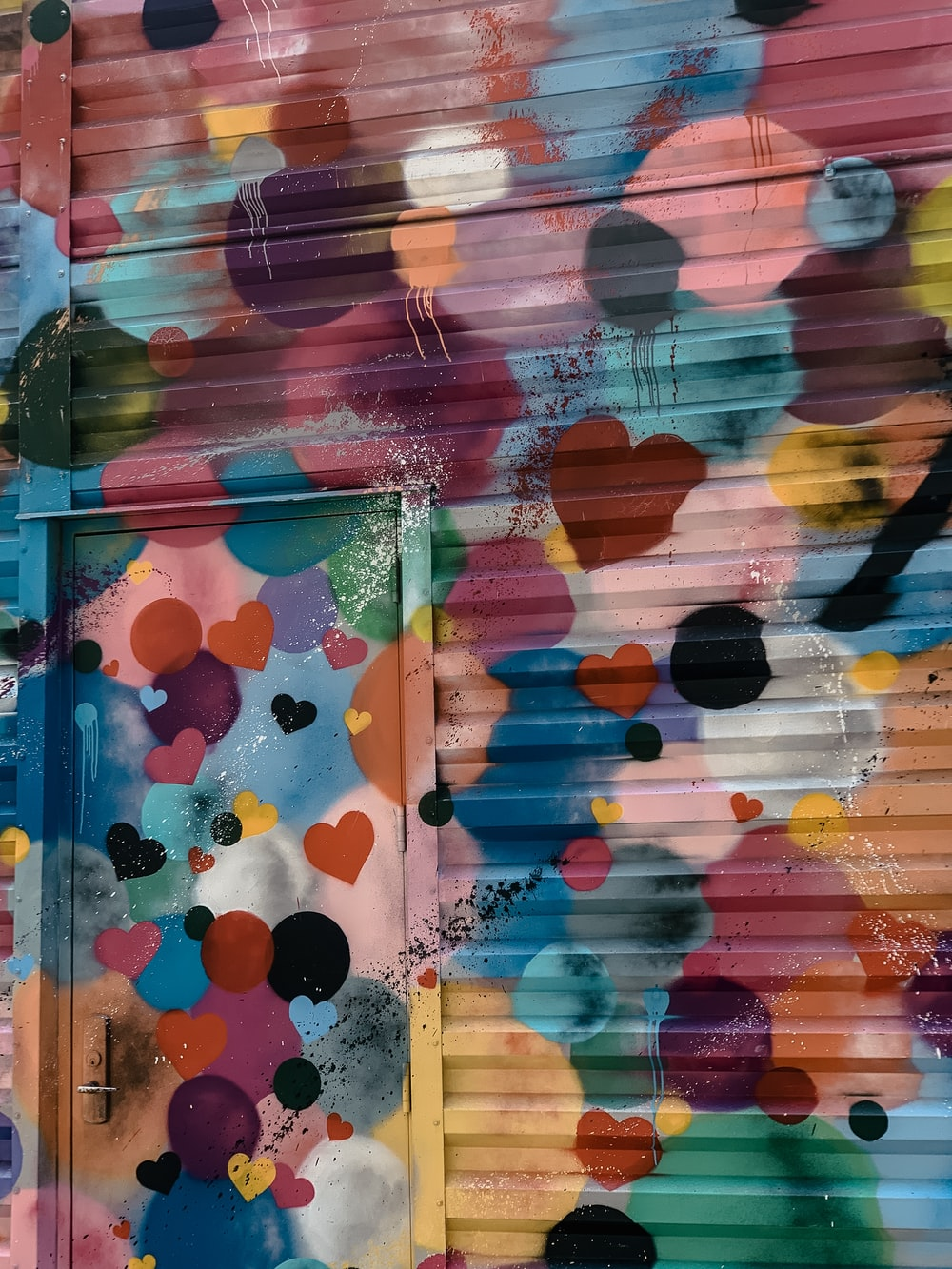 colorful hearts painted on a metal wall