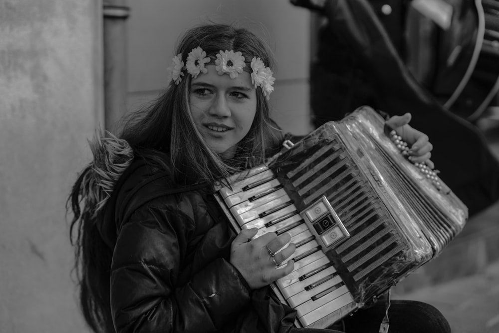 grayscale photo of a woman playing an accordion