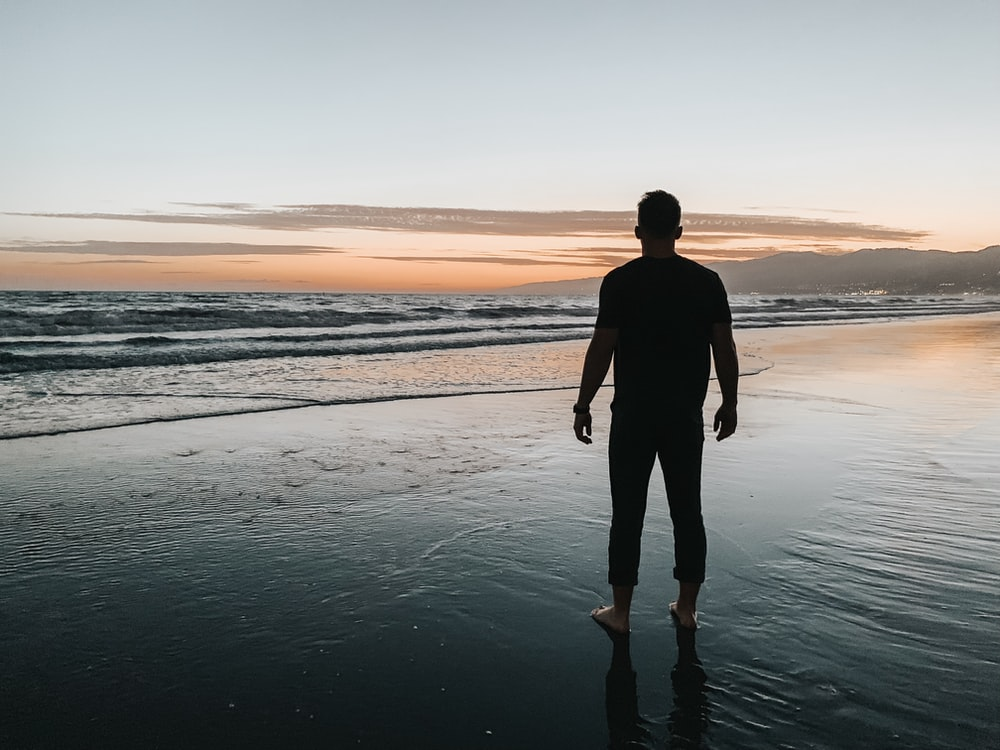 man standing at the beach during sunset
