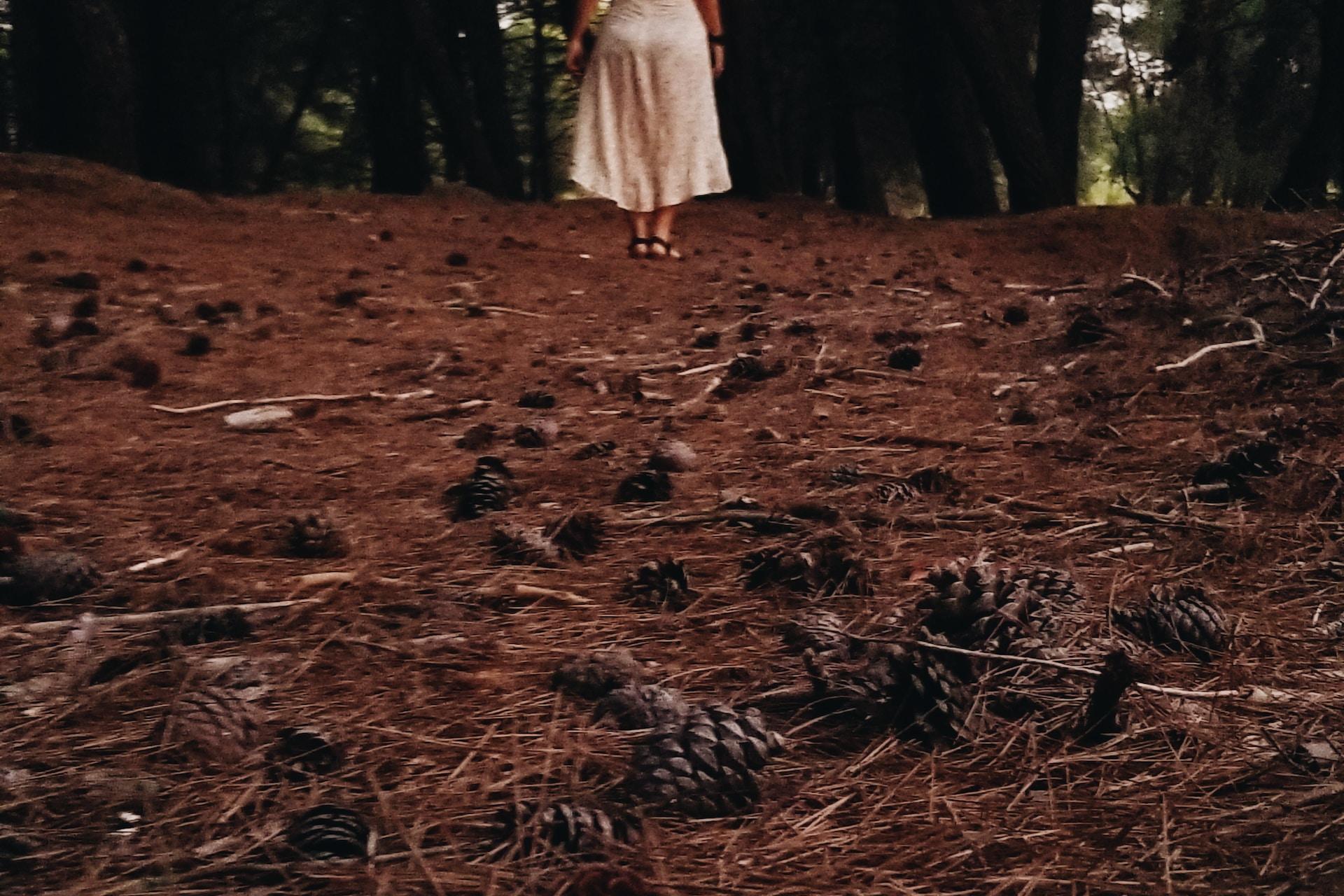 woman wearing white standing on brown soil