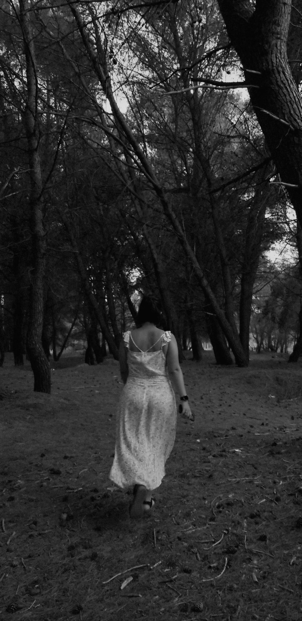 grayscale photography of woman walking surrounded by trees