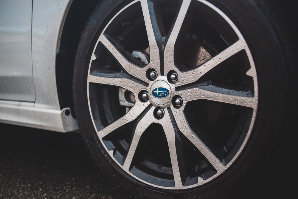 white Subaru car with chrome wheels