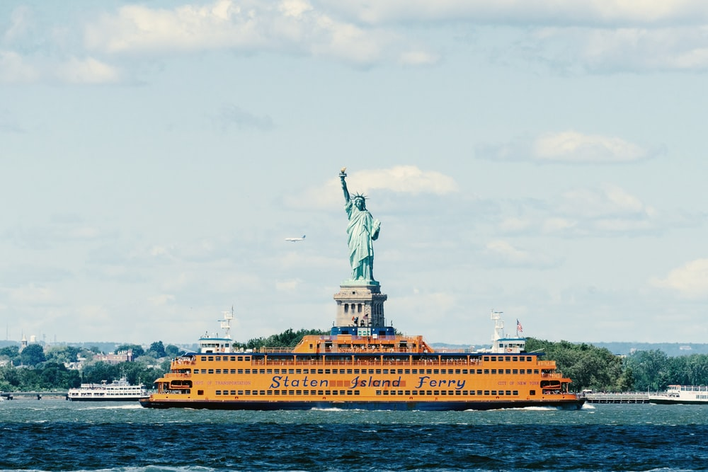 Yellow Boat On Body Of Water Near Statue Of Liberty On