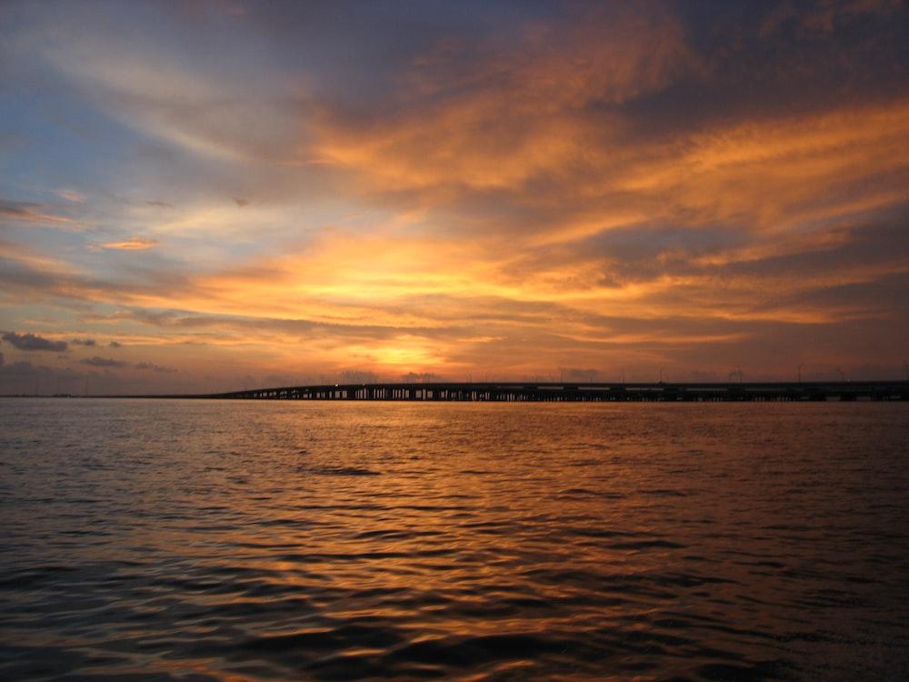 body of water near bridge at golden hour