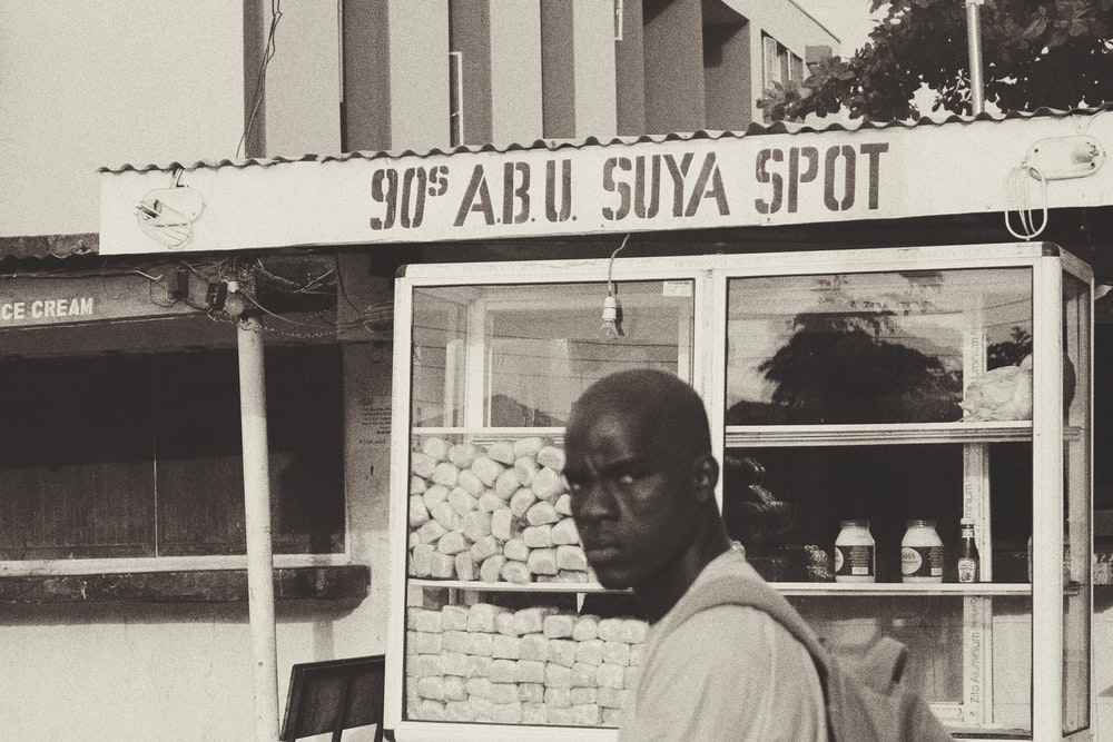 grayscale photo of man standing near food stall