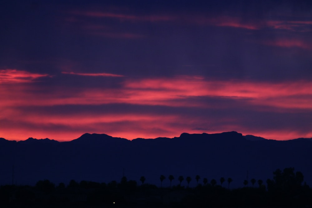 silhouette of mountain under red sky during golden hour