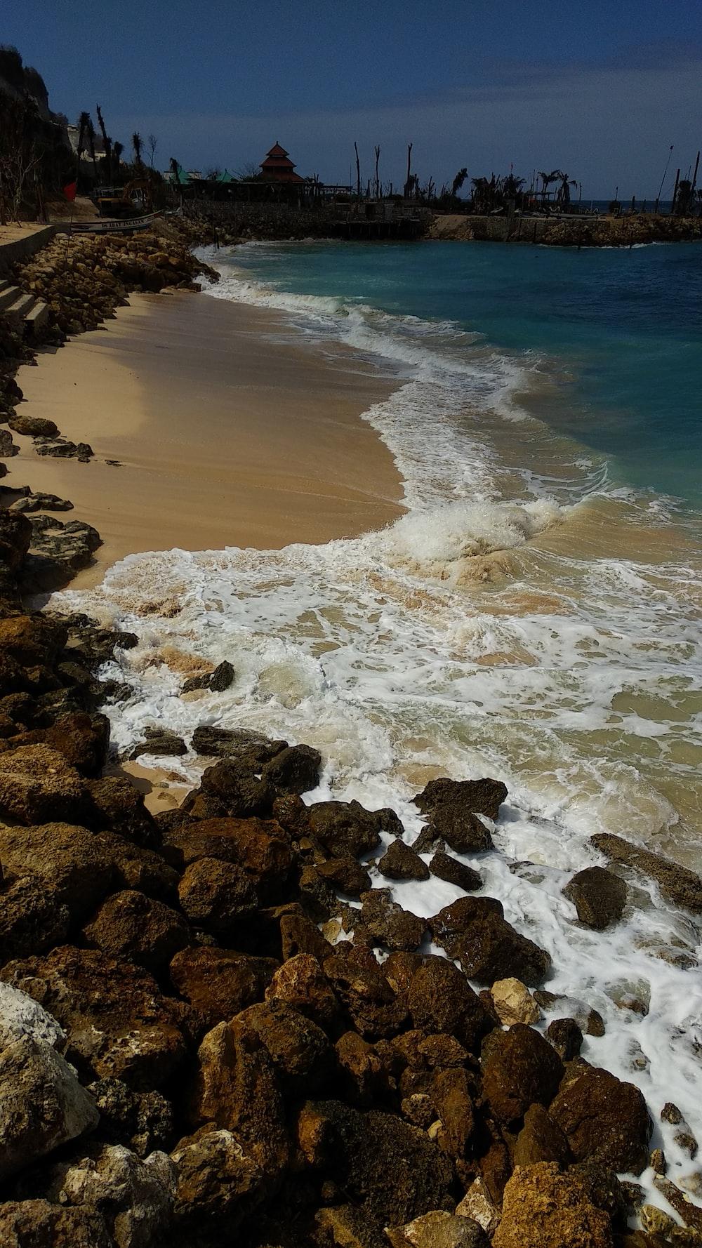 rocks beside body of water at daytime