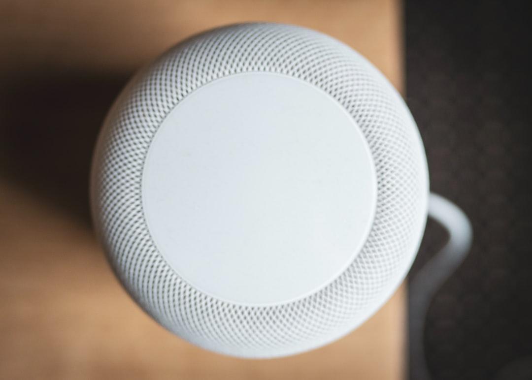 Apple HomePod speaker on wooden table.